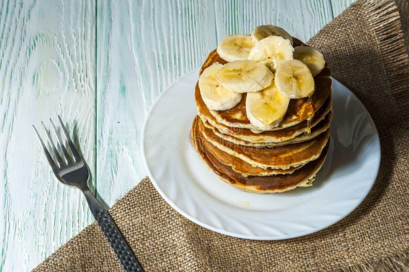 堆与香蕉切片和蜂蜜的自创薄煎饼在有叉子的白色板材和在木背景的亚麻布餐巾 免版税库存图片