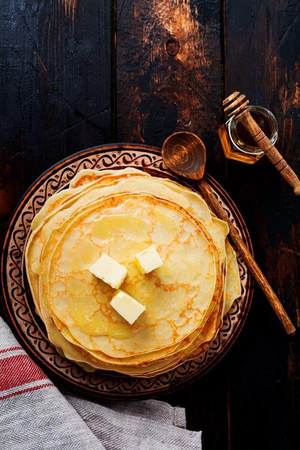 堆与黄油、牛奶和蜂蜜片断的自创稀薄的薄煎饼在老土气陶瓷板材 免版税库存图片