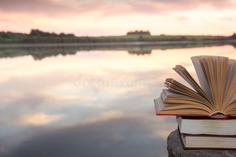 堆书和开放精装书在被弄脏的自然风景背景预定反对与后面光的日落天空 复制空间,到 免版税库存图片