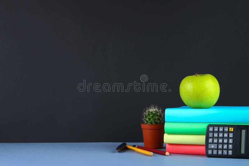 堆书和文具在黑板背景 工作书桌,教育,学校 免版税库存图片
