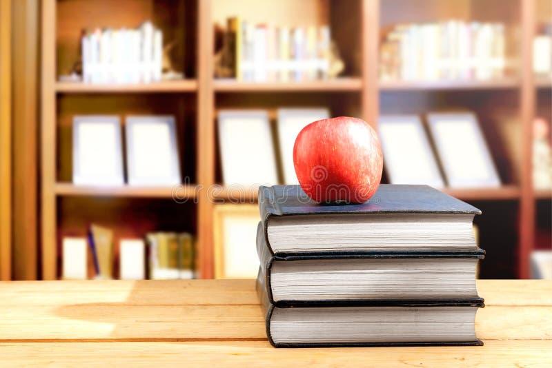 堆书用在木桌上的苹果在图书馆里 库存图片