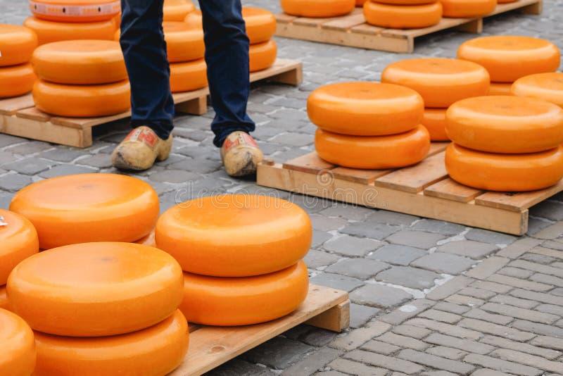 堆乳酪和传统荷兰鞋子在荷兰扁圆形干酪 免版税库存照片