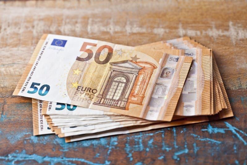 堆五十张欧元钞票 50€在木桌上堆积的货币笔记 免版税库存照片
