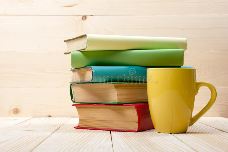 堆五颜六色的书、开放书和杯子在木桌上 回到学校 复制空间 免版税库存图片