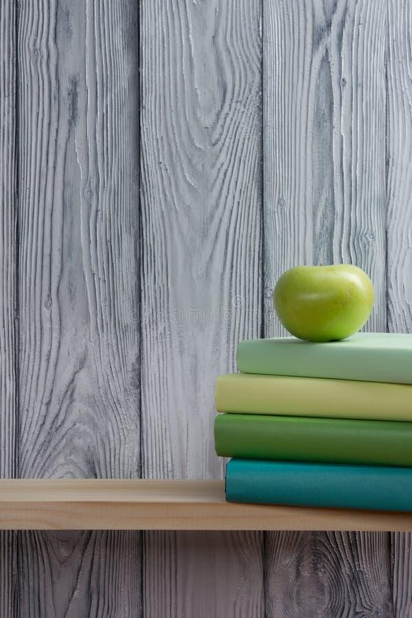 堆五颜六色的书和绿色苹果在木桌上 回到学校 复制空间 库存图片