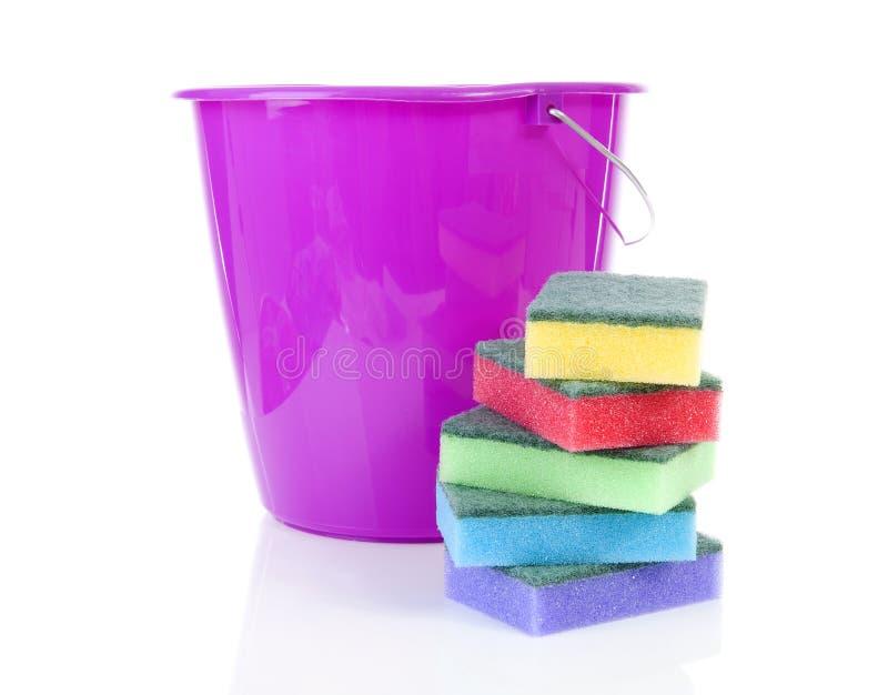 堆五颜六色的海绵去壳机和桃红色桶在白色backg 库存图片