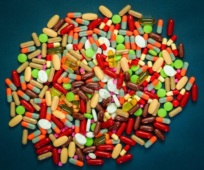 堆五颜六色的片剂和胶囊药片在蓝色背景 与合理的概念的抗药性抵抗和药物用途 免版税库存图片
