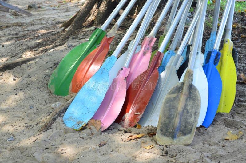 堆五颜六色的皮船在沙子用浆划在海滩 免版税图库摄影