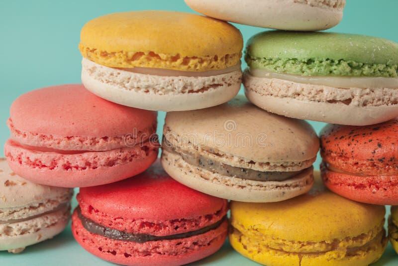 堆五颜六色的蛋白杏仁饼干加起象一个塔在turquose淡色背景(选择聚焦) -特写镜头中 免版税库存图片