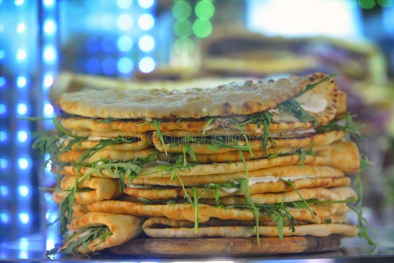 堆传统意大利食物Piadina Romagnola用新鲜的蕃茄无盐干酪和火箭沙拉 图库摄影