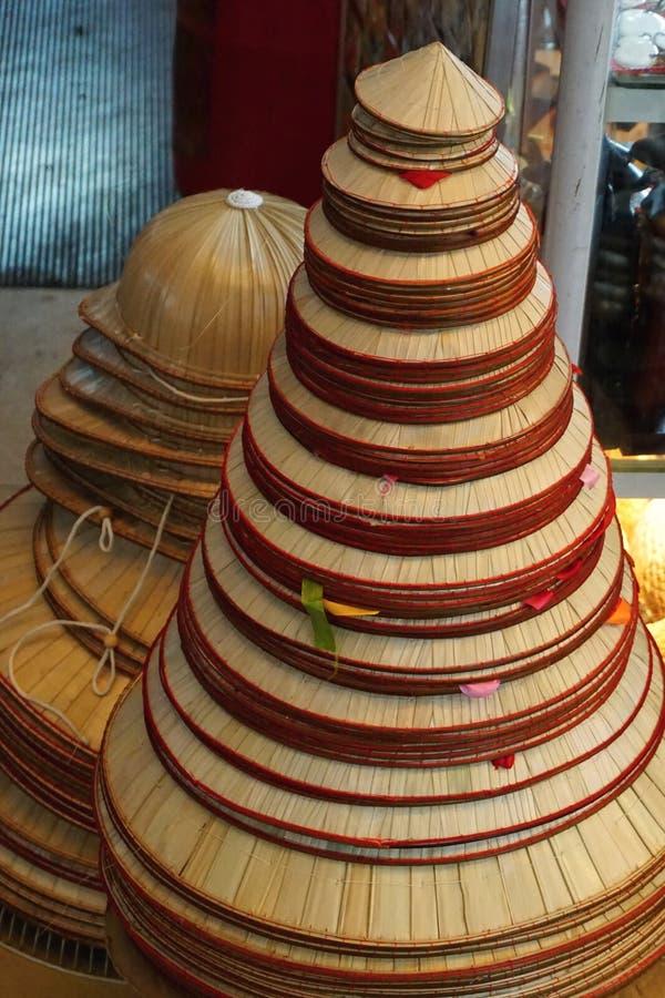 堆传统棕榈叶圆锥形帽子在一家商店在河内,越南 免版税库存图片