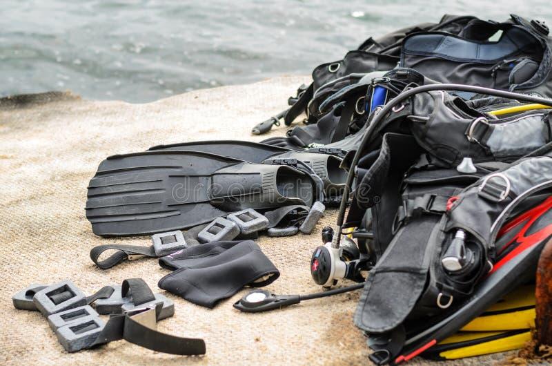 堆佩戴水肺的潜水在船坞的设备干燥 库存照片