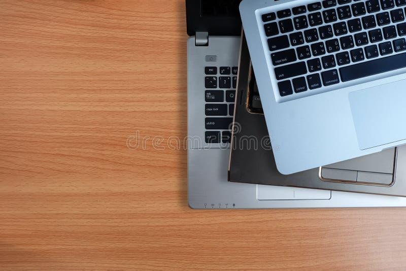 堆使用的便携式计算机,在木背景 顶视图拷贝空间 免版税库存照片