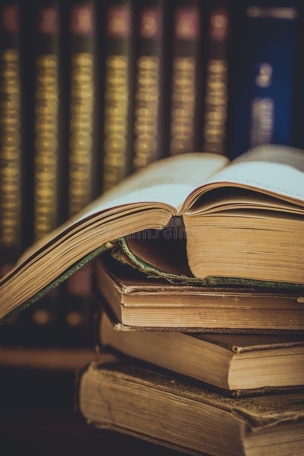 堆使用的老被打开的书,与被铭记的盖子在背景中,大学教育的容量,读概念,被定调子 免版税图库摄影