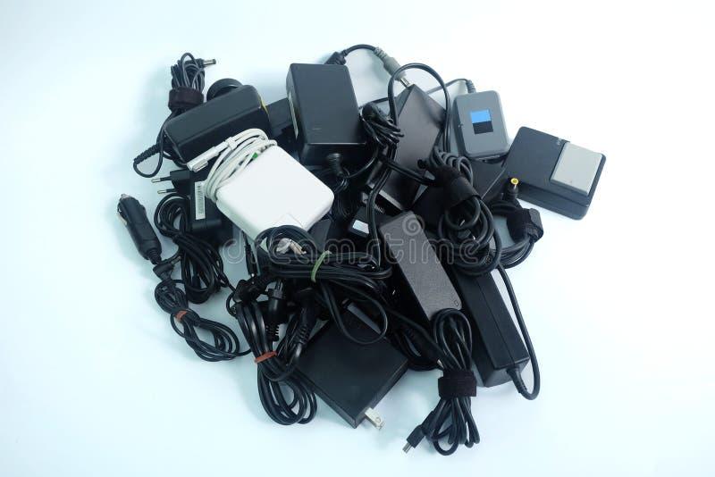 堆便携式计算机损坏的或老使用的适配器力量充电器在白色的 免版税库存图片