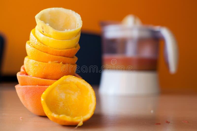 堆充分新近地被紧压的柑橘和一个被紧压的桔子在前面和榨汁器汁液在背景中 免版税库存图片