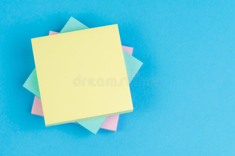 堆关于坚实蓝色背景的稠粘的笔记与桃红色,蓝色和黄色在与拷贝空间的上面写的消息使用作为备忘录 免版税库存图片