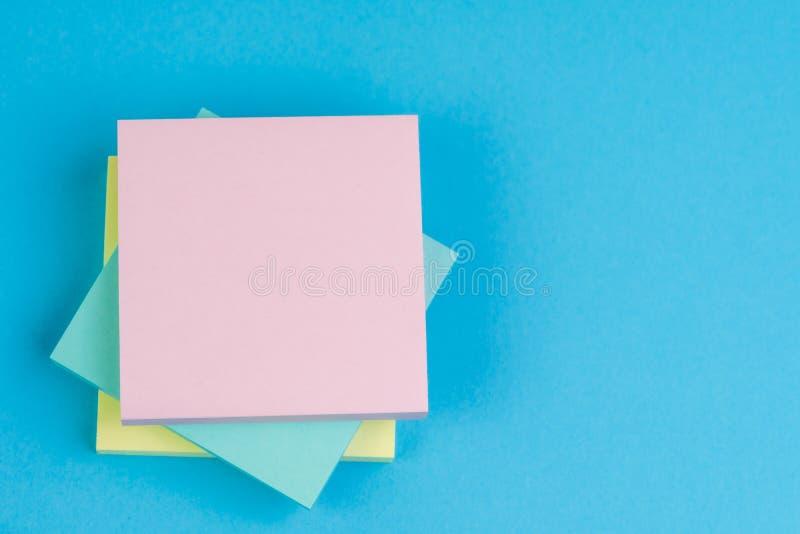 堆关于坚实蓝色背景的稠粘的笔记与黄色,蓝色和桃红色在与拷贝空间的上面写的消息使用作为备忘录 库存图片