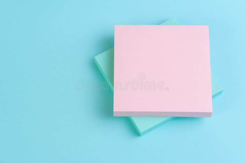 堆关于蓝色背景的稠粘的笔记与在上面的桃红色与写的消息拷贝空间使用当启发文本,备忘录, 库存照片