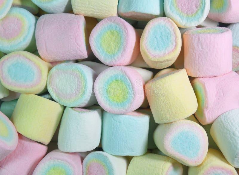 堆关闭粉红彩笔,黄色,蓝色上色了背景的蛋白软糖 免版税库存图片