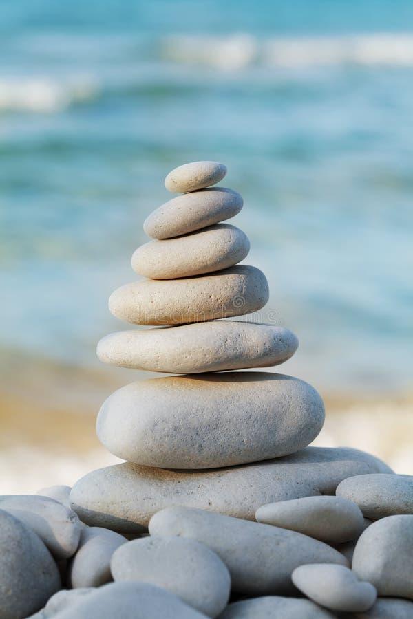 堆反对海的白色小卵石石头温泉、平衡、凝思和禅宗题材的 库存图片