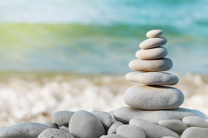 堆反对蓝色海背景的白色小卵石石头温泉、平衡、凝思和禅宗题材的 免版税图库摄影