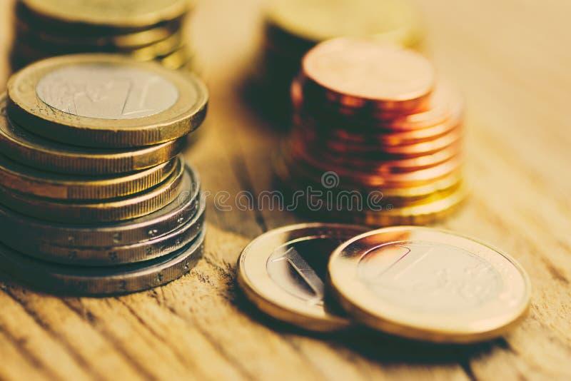 堆另外价值光滑的白色和黄色欧洲硬币在木背景的 财务投资库存储款预算 库存照片