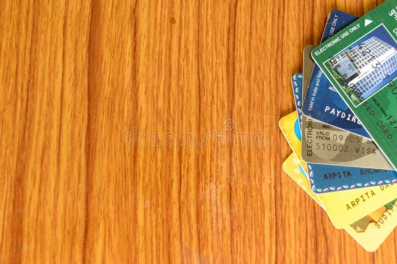 堆另外银行信用卡被安置在木桌边缘  企业财务经济产品 购物背景 免版税库存照片
