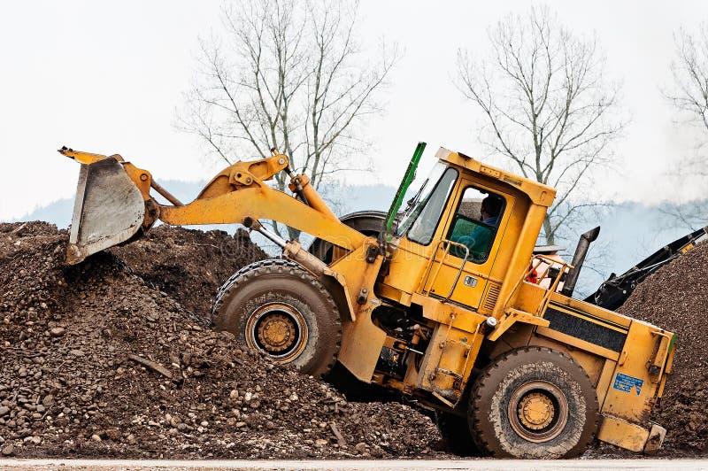 堆土的黄色重的轮子装载者在岩石和土分离站点 库存照片