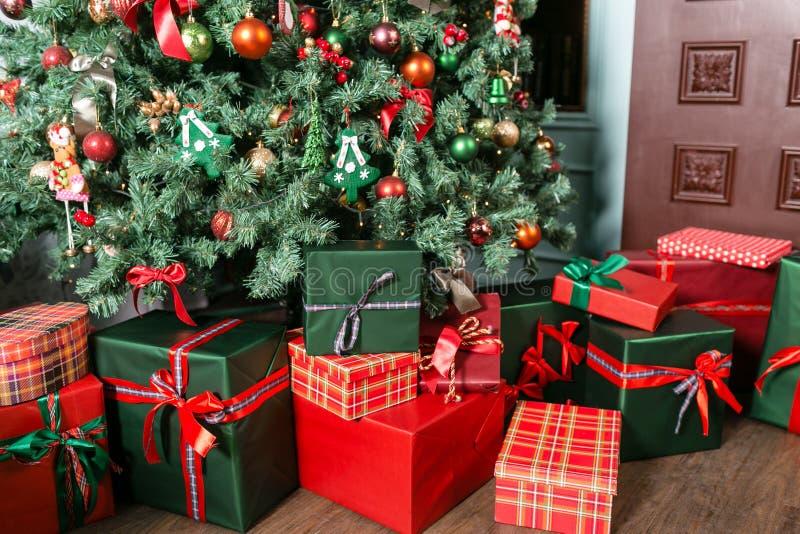堆圣诞节礼物特写镜头在圣诞树下 绿色存在红色 库存照片