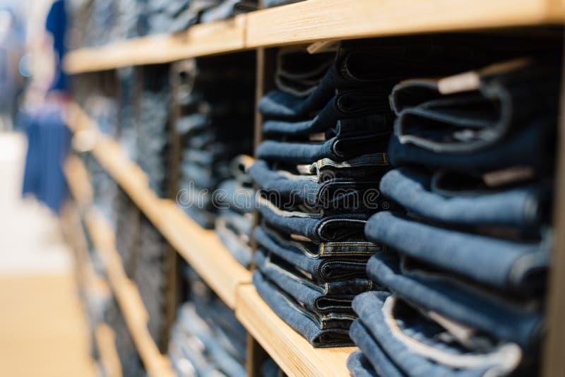 堆在一个商店窗口的牛仔裤在商店 免版税库存照片