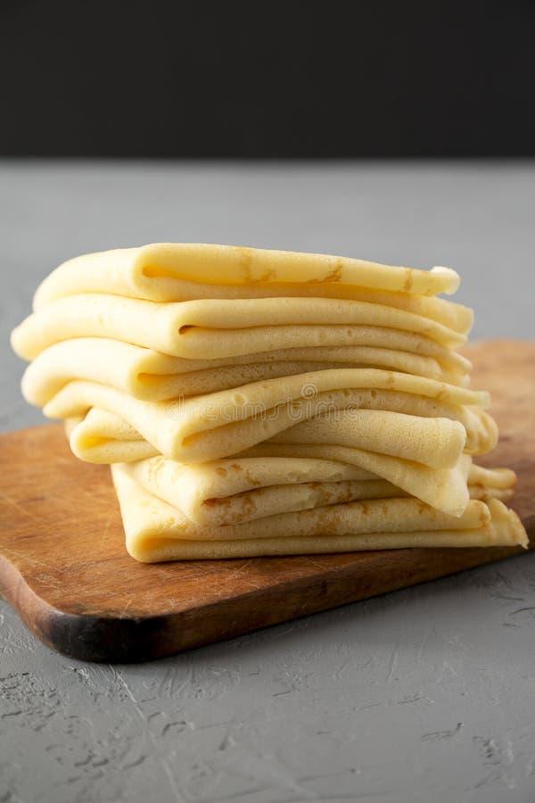 堆在一个土气木板的鲜美俄式薄煎饼在具体背景,侧视图 r 免版税库存图片