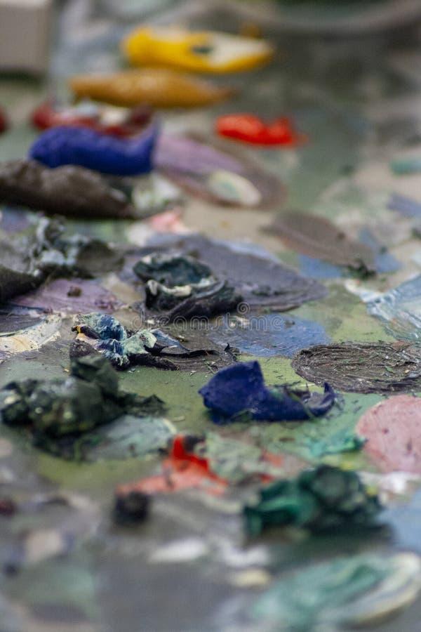 堆在一个杂乱艺术委员会的油漆 库存照片