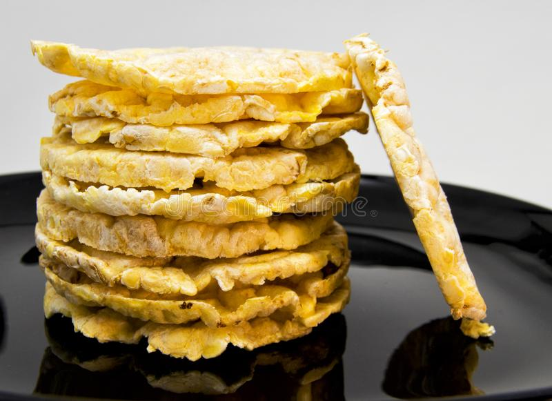 堆在一个黑盘的米和玉米crakers 对素食和健康食物概念 免版税库存图片