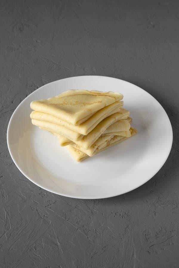 堆在一块白色板材的鲜美俄式薄煎饼在具体背景,侧视图 r 免版税库存图片