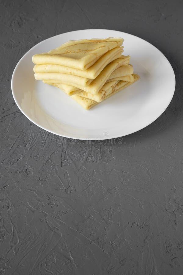 堆在一块白色板材的鲜美俄式薄煎饼在灰色背景,侧视图 r 免版税库存照片