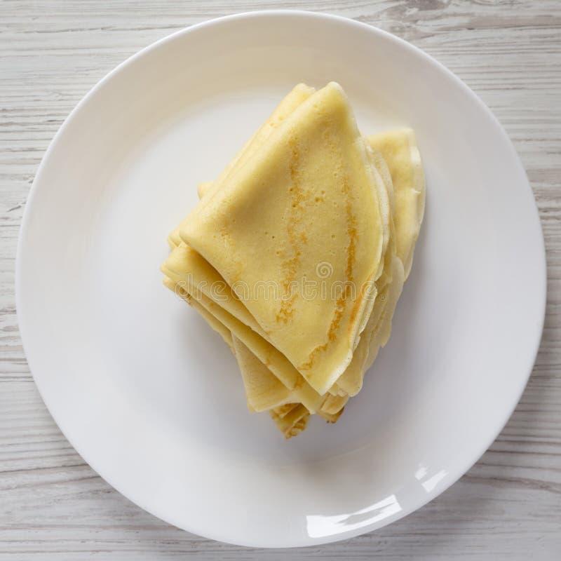 堆在一块白色板材的鲜美俄式薄煎饼在白色木表面,顶视图 r r 免版税库存照片