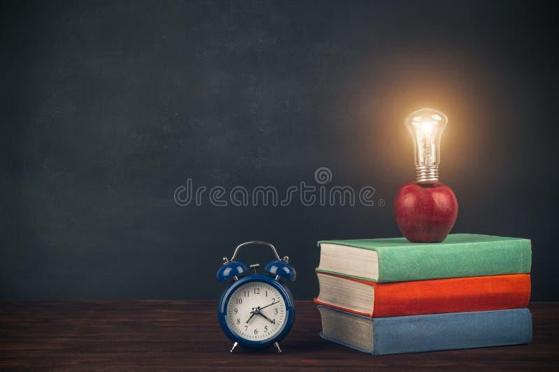 堆在一张木桌、苹果与电灯泡和闹钟上的多彩多姿的课本 回到学校 免版税库存图片