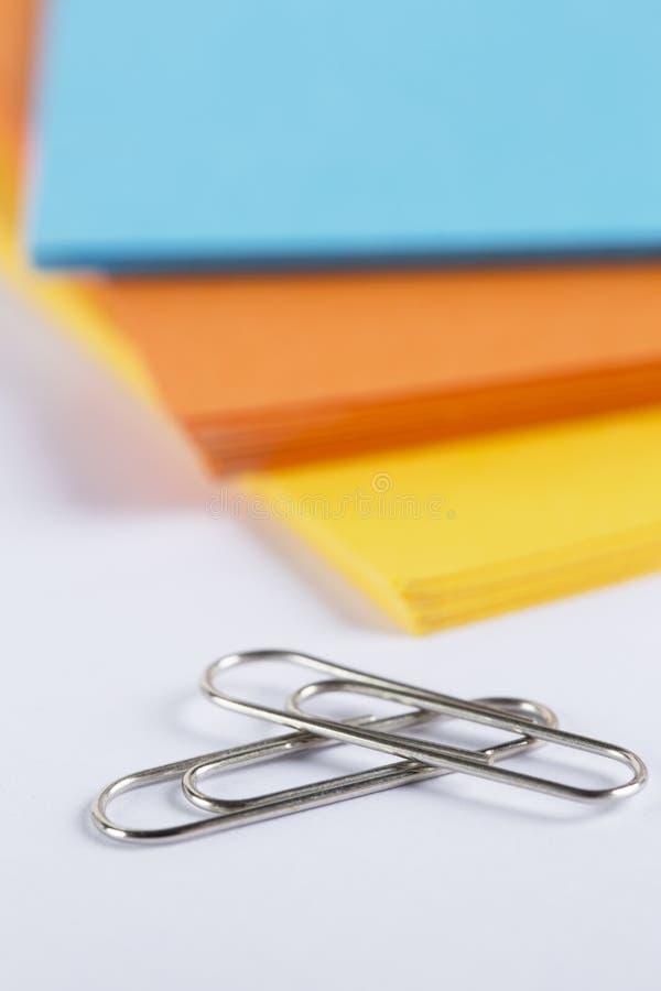 堆在一张白色桌上的色的纸 图库摄影