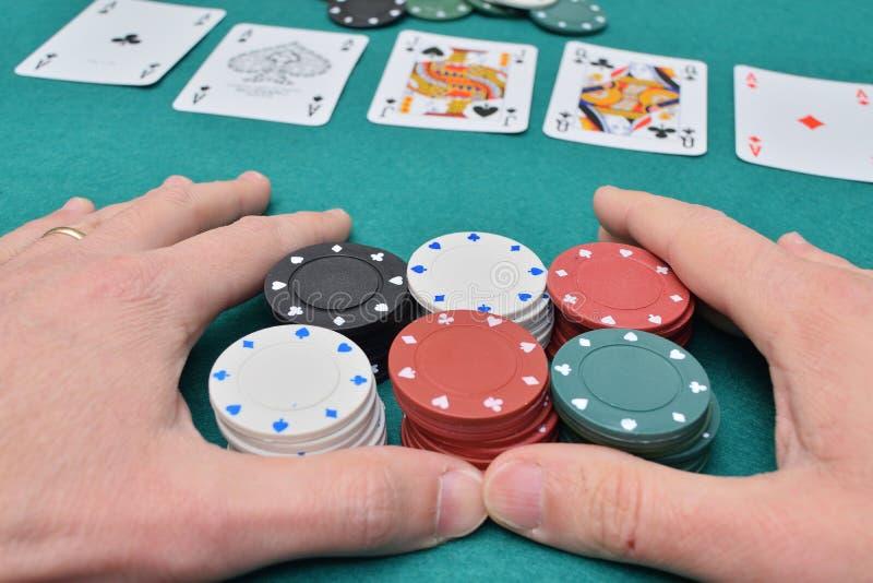堆在一张赌博的桌上的纸牌筹码在两只手上和卡片 库存照片