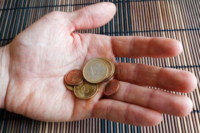 堆在人的人手上的欧洲硬币 免版税库存照片