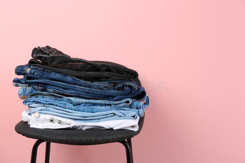 堆在凳子的不同的牛仔裤 免版税图库摄影