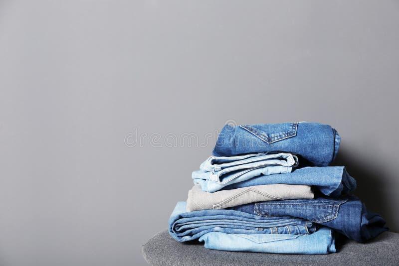 堆在凳子的不同的牛仔裤 免版税库存照片