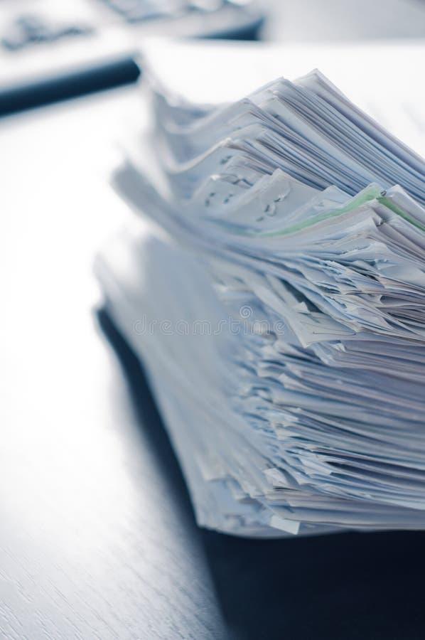 堆在办公室桌上的纸 免版税库存图片