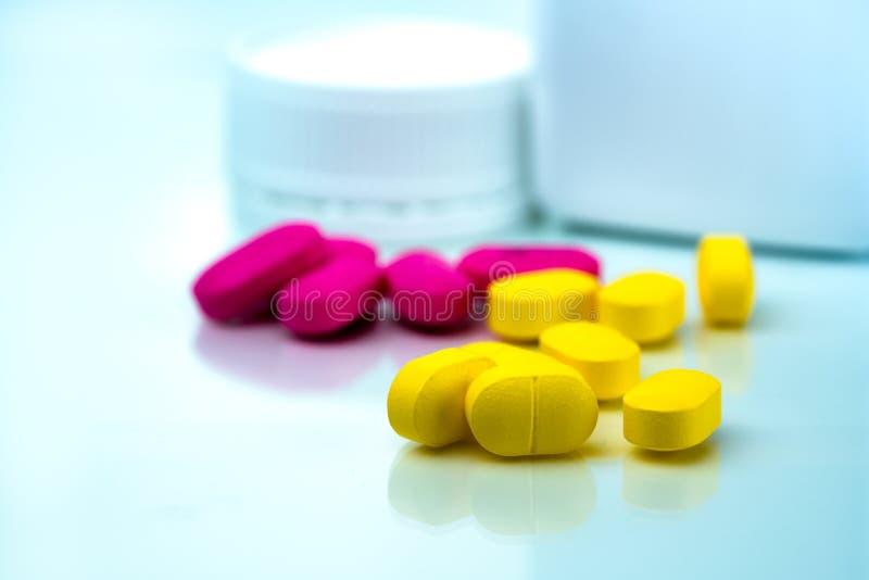 堆在塑料药瓶被弄脏的背景的黄色和桃红色片剂药片有拷贝空间的 安心痛苦的异丁苯丙酸 免版税库存照片