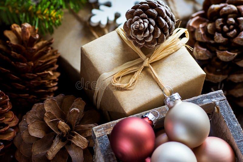 堆在工艺纸五颜六色的球大杉木锥体绿色杉树分支雪剥落包裹的圣诞节和新年礼物盒 图库摄影