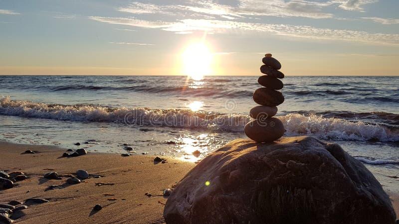 堆在平衡的不同的石头在海滩日落 库存图片