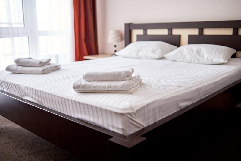 堆在床上的白色干净的毛巾在现代旅馆卧室内部,拷贝空间 库存图片