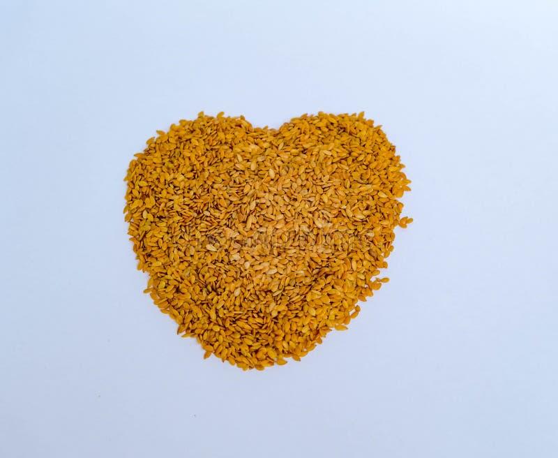 堆在心形的金黄亚麻籽在白色 图库摄影