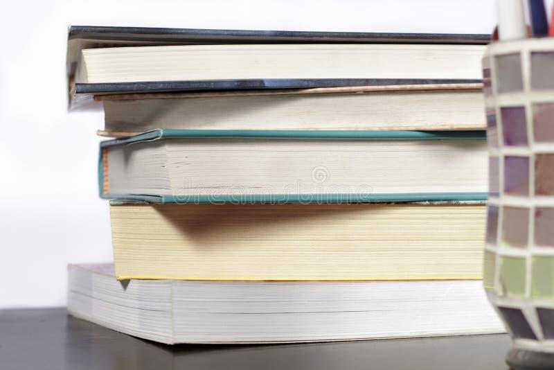 堆在木书桌和白色背景上的书 免版税库存照片